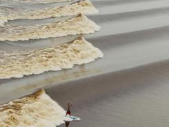 Brazilian surfer Bruno Santos rides a wave during a tidal bore along Indonesia's Seven Ghosts river.