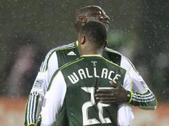 Portland Timbers' Rodney Wallace is hugged by teammate Mamadou Danso after scoring a goal against the Chicago Fire in the first half of their game in Portland, Ore.