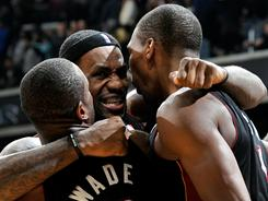Dwyane Wade, left, LeBron James, center, and Chris Bosh hope for more celebrations like this during the NBA playoffs. The Heat open at home against the 76ers on Saturday.