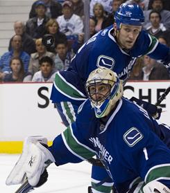 Vancouver goalie Roberto Luongo and Sami Salo eye a flying puck during the Canucks' first-round game against the Chicago Blackhawks in Vancouver.