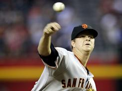 San Francisco pitcher Matt Cain delivers a pitch against the Arizona Diamondbacks during the first inning on Friday. The Giants won 5-2. Cain threw 6 scoreless innings.