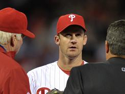 Phillies starter Roy Oswalt confers with manager Charlie Manuel, far left, and others after he strained his back in Friday's 4-3 loss to the Marlins.