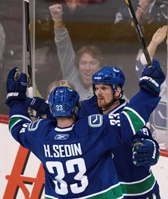 The Canucks' Daniel Sedin, right, celebrates his goal against the Blackhawks with his twin brother Henrik Sedin during Game 2 of their first-round playoff series.