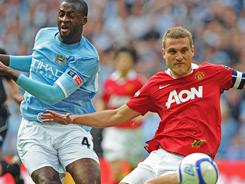 Manchester City's Yaya Toure, left, vies for the ball with Manchester United's Nemanja Vidic during their FA Cup semifinal on Saturday. Toure had a goal in City's 3-1 win.