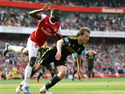 Arsenal midfielder Emmanuel Eboue collides with Liverpool's Lucas Leiva to concede a last-minute penalty. Dirk Kuyt scored from the spot and the game ended 1-1. Arsenal is six points behind Manchester United.