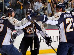 Predators center Mike Fisher, left, skates over to teammates after putting his team ahead 4-3 in the third period.