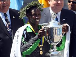 Geoffrey Mutai holds his trophy after winning the men's division of the 115th running of the Boston Marathon.