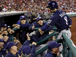 Ryan Braun celebrates with teammates after driving in and scoring a run in the 12th inning to give the Brewers a tough 6-3 win over the Phillies.