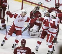 Detroit Red Wings Kris Draper, left, Patrick Eaves, middle, and Darren Helm celebrate a first-period against the Phoenix Coyotes in Game 4 of their first-round playoff series in Glendale, Ariz.