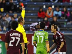 Colorado Rapids midfielder Brian Mullan, second from right, is served with red card after a sliding tackle on Seattle Sounders FC midfielder Steve Zakuani (on ground) in the first half of their match Friday night. Fredy Montero scored his first goal since August 2010 to help the Sounders to a 1-0 win.