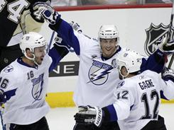 The Lightning's Vincet Lecavalier celebrates with Simon Gagne (12) and Teddy Purcell (16) after Lecavalier scored a first-period goal. Gagne scored twice and Purcell had three assists in the 8-2 rout.