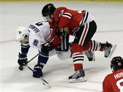 The Canucks' Dan Hamhuis, left, gets checked by the Blackhawks' Ben Smith during Game 6 on Sunday in Chicago.