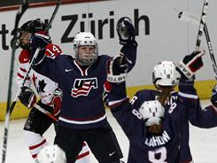U.S. forward Jocelyne Lamoureux, center, celebrates after scoring the first goal during the IIHF World Women Championship gold medal game between the USA and Canada in Zurich, on April 25.