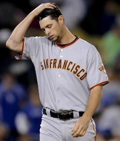 San Francisco Giants rookie Brandon Belt reacts as he walks back to his dugout after being left on third base in the eighth inning of a baseball game against the Los Angeles Dodgers, Sunday, April 3, 2011.