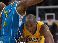 Lakers guard Kobe Bryant drives past the Hornets' Trevor Ariza during first-half action. Bryant shook off a sprained ankle, scoring 19 points in Los Angeles' win over New Orleans.