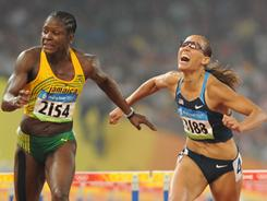 In this file photo from the 2008 Beijing Summer Olympics, Lolo Jones, right, struggles across the finish line after hitting a hurdle and dropping to seventh place. Delloreen Ennis-London of Jamaica, left, finished fifth.