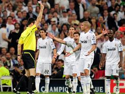 Referee Wolfgang Stark displays a red card for Real Madrid's Pepe, right, during the second half against Barcelona.