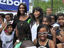 Venus, left, and Serena Williams hang out with young tennis players at the Southeast Tennis and Learning Center on Thursday in Washington.