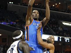 Oklahoma City Thunder's Kevin Durant (35) shoots over Memphis Grizzlies' Zach Randolph, left, and Shane Battier during a game in March.