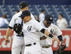 Yankees outfielders, from left, Brett Gardner, Nick Swisher and Curtis Granderson celebrate New York's win over the Blue Jays.