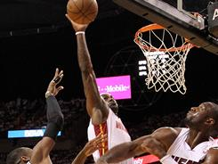 Heat forward LeBron James, center, blocks a shot by the Celtics' Rajon Rondo as Dwyane Wade helps defend during Game 1 of their Eastern Conference semifinal. James and Wade scored 22 and 38 points, respectively, as Miami beat Boston 99-90 on Sunday.
