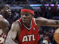 The Hawks' Joe Johnson, right, drives around the Bulls' Ronnie Brewer during the second quarter of Game 1 in Chicago. Led by Johnson's 34 points, including a perfect 5-for-5 on three-pointers, Atlanta won 103-95.