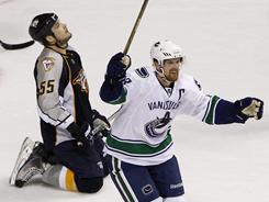 Henrik Sedin, right, celebrates as Shane O'Brien kneels after Ryan Kesler, not shown, scored the game-winning overtime goal to give the Canucks the 3-2 victory over the Predators.