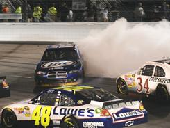 Jimmie Johnson (48) heads to the bottom of the track at Richmomd International Raceway to avoid the spin-out by Brad Keselowski (2) as David Gilliland (34) tries to maneuver his car during Saturday's Sprint Cup race.