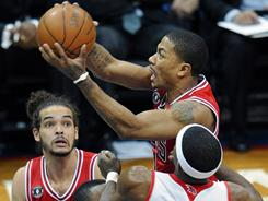 Chicago Bulls point guard Derrick Rose, top, drives between Atlanta Hawks defenders as Bulls center Joakim Noah, left, looks on in the first quarter of the Bulls' Game 3 win Friday of their Eastern Conference semifinal series.