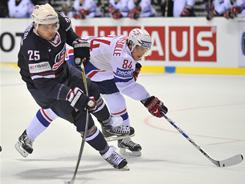 Nick Palmieri of the United States shoots the puck as France's Kevin Hecquefeuille plays defense during an IIHF World Championship Group F qualification game on Saturday.