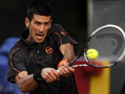 Novak Djokovic of Serbia hammers a backhand during his victory Sunday against Rafael Nadal of Spain in the final of the Madrid Open.