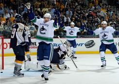 From left to right, the Vancouver Canucks' Daniel Sedin, Henrik Sedin, and Ryan Kesler celebrate a goal against the Nashville Predators in Game 6 of their second-round playoff series in Nashville.