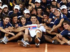 The ball kids from the Madrid Open surround Novak Djokovic of Serbia following his victory Sunday against Rafael Nadal. Djokovic has six titles and an unbeaten 32-0 record in 2011.