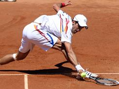Novak Djokovic of Serbia stretches for a backhand during his victory Wednesday against Lukasz Kubot of Poland at the Italian Open in Rome.