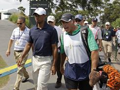 Tiger Woods and caddie Steve Williams leave the course after nine holes during the first round of The Players Championship on Thursday in Ponte Vedra Beach, Fla.
