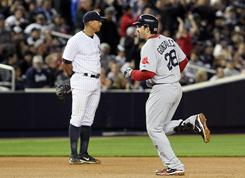 Boston Red Sox first baseman Adrian Gonzalez, right, rounds the bases after hitting a three-run home run as the Yankees' Alex Rodiguez looks on during their game in New York.