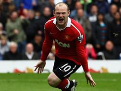 Machester United's Wayne Rooney celebrates after scoring on a penalty kick in a Premier League match against Blackburn on Saturday. Manchester United clinched its 19th title with the draw.