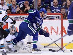 Canucks captain Henrik Sedin backhands the puck past Sharks goalie Antti Niemi for the game-winning goal.