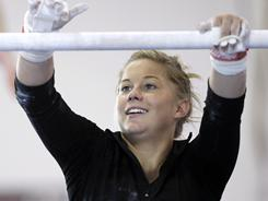 In this photo taken Nov. 15, 2010, gymnast Shawn Johnson chalks up the bar during a workout at Chow's Gymnastics in West Des Moines. 