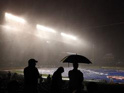 Fans sit through a downpour of rain during a game between the Chicago Cubs and the St. Louis Cardinals.