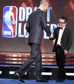 NBA deputy commissioner Adam Silver, left, congratulates Nick Gilbert, 14, the son of Cleveland Cavaliers owner Dan Gilbert, after it was announced that Cleveland won the 2011 NBA basketball draft lottery in Secaucus, N.J.