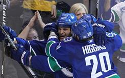 The Canucks' Kevin Bieksa, left, celebrates his goal with teammates during the second period against the San Jose Sharks in Game 2 of the Western Conference finals in Vancouver.