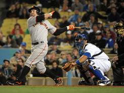 The Giants' Cody Ross (13) follows through on what proved to be a game-winning three-run home run in the ninth inning Wednesday night against the Dodgers. San Francisco won 8-5.