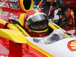 IndyCar Series driver Helio Castroneves gets strapped into his car during practice for the Indianapolis 500. The three-time winner and the field are prepping for qualifying on Saturday while dealing with increment weather on the track.
