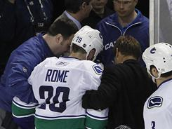 Vancouver Canucks defenseman Aaron Rome is helped off the ice after being checked by San Jose Sharks left wing Jamie McGinn.