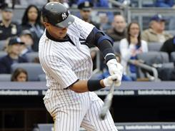 Yankees' Alex Rodriguez hits an RBI infield single during the seventh inning against the Mets.