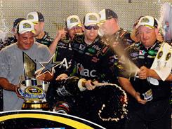 Flanked by his team, Carl Edwards celebrates in victory lane after driving to first place in Saturday's Sprint All-Star Race at Charlotte Motor Speedway. He also tore up the front end of his No. 99 Ford driving through the infield after the race.