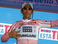 Spanish cyclist Alberto Contador celebrates on the podium after winning the 16th stage of the Giro d'Italia from Belluno to Nevegal on May 24. Alberto Contador won the 12.7-kilometer mountain time-trial from Belluno to Nevegal, to retain his grip on the leader's pink jersey.