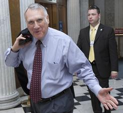 Sen. Jon Kyl, R-Ariz., walks with an aide outside of the Senate chamber on Capitol Hill in Washington May 19.