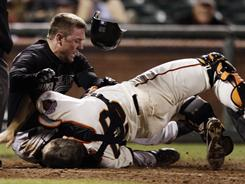 Scott Cousins, top, scored the go-ahead run after Buster Posey dropped the ball in a scary collision at the plate. Posey was helped off the field moments later.